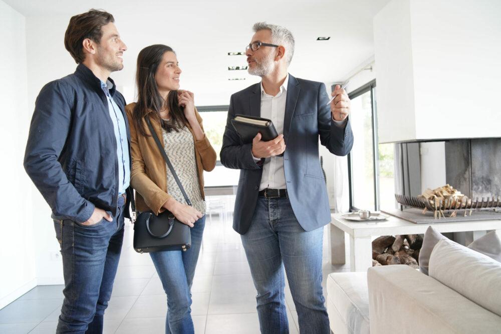 Immobilienmakler zeigt jungem Paar die Räume